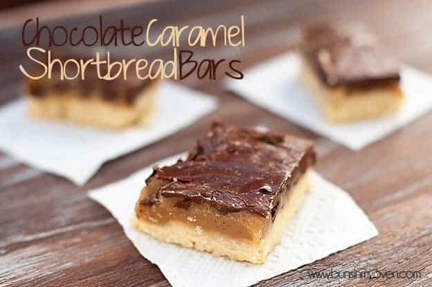 A close up of a few shortbread bars topped with caramel and chocolate on a table.