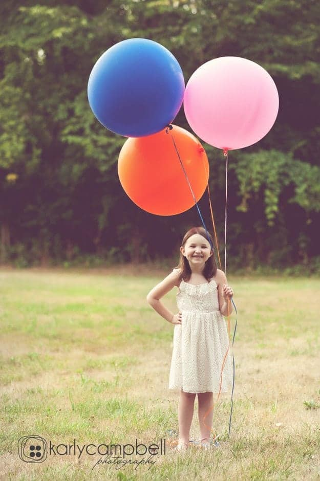 A person holding three large balloons.