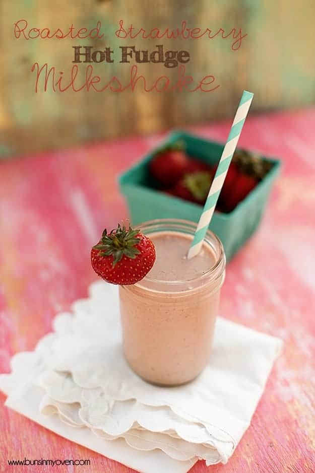A strawberry milkshake in a glass jar with a strawberry on the rim