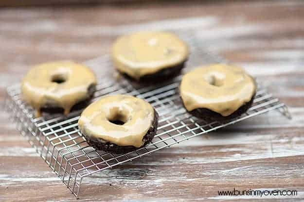 Four donuts with peanut butter icing on a cooling wire rack.