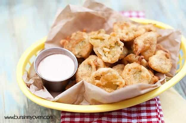 A close up of an appetizer basket with fried pickles and ranch dressing in it.