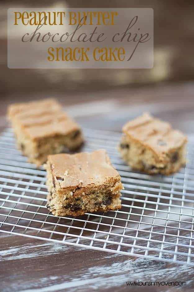 Three peanut butter chocolate chip snack cakes on a wire cooling rack.