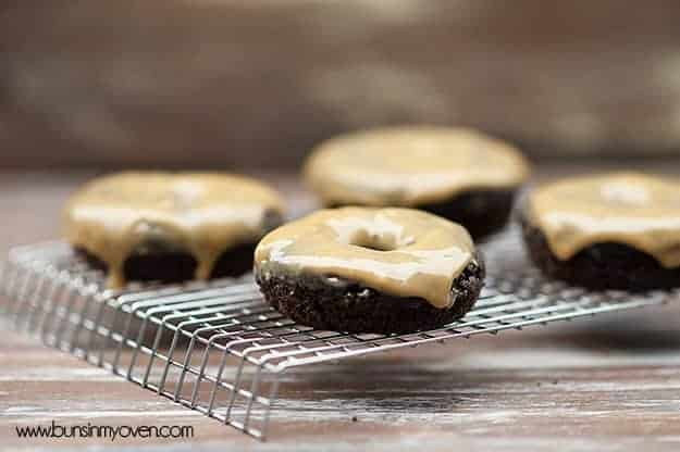 A chocolate donut with peanut butter frosting on a cooling rack.