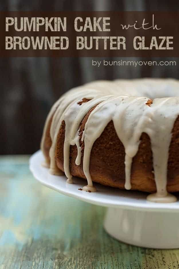 A pumpkin cake on cake stand covered with brown butter glaze