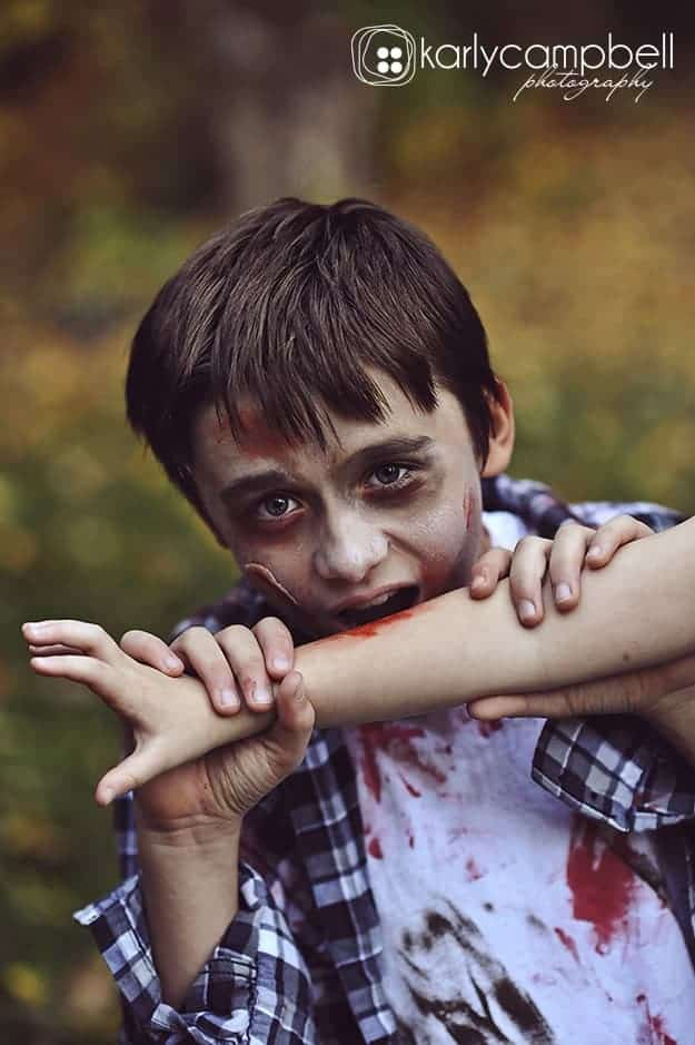 a zombie boy biting a persons arm
