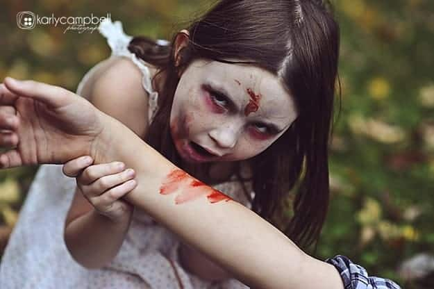 a zombie girl taking a bite out of an arm