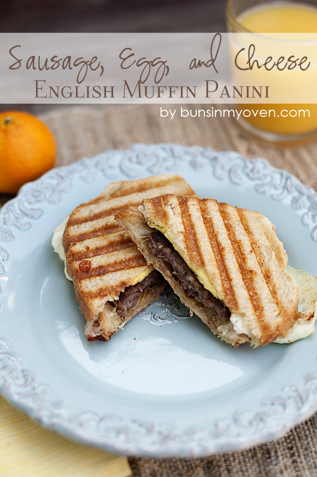 A panini cut in half on a decorative plate with orange juice in the background.